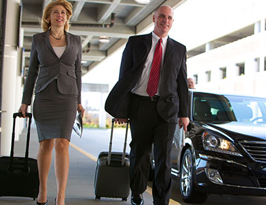 Two business executives walk along the sidewalk of Richmond International Airport after being dropped off by a James Limousine chauffeur.