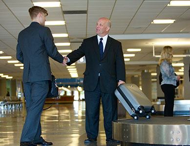 A James Limousine driver picking up a clients baggage at an airport while shaking his hand.
