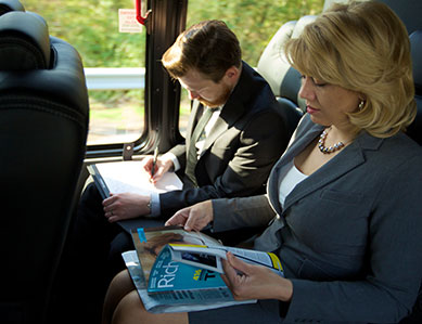 A business executive woman flipping through a magazine while her male colleague writes in a notepad beside her on a luxury bus.
